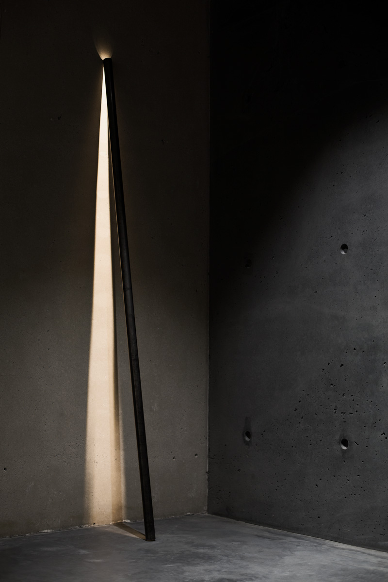 A photograph of Silhouet Lighting Tube on a concrete wall at ETQ store by Poppyonto