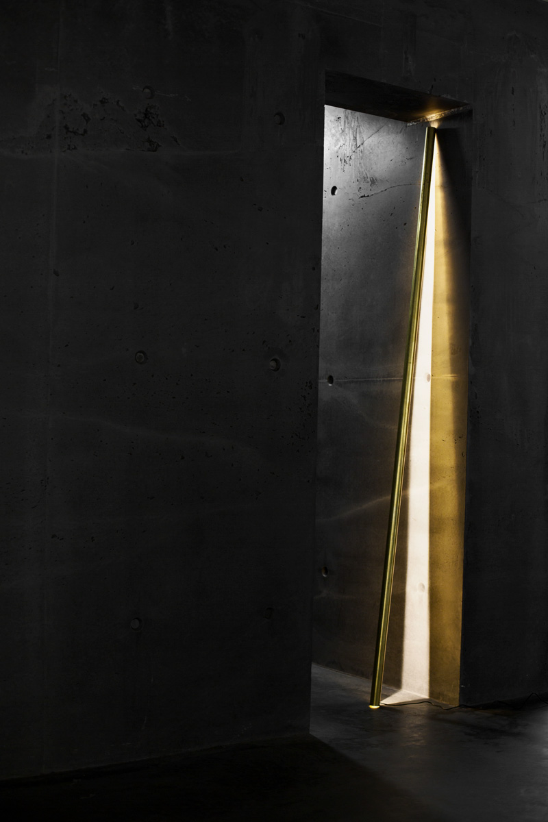 A photograph of Silhouet Lighting Tube in a concrete doorway at ETQ Store Amsterdam by Poppyonto